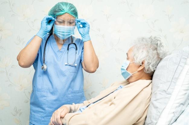 Medico asiatico che indossa uno schermo facciale e una tuta dpi per proteggere il coronavirus covid-19.