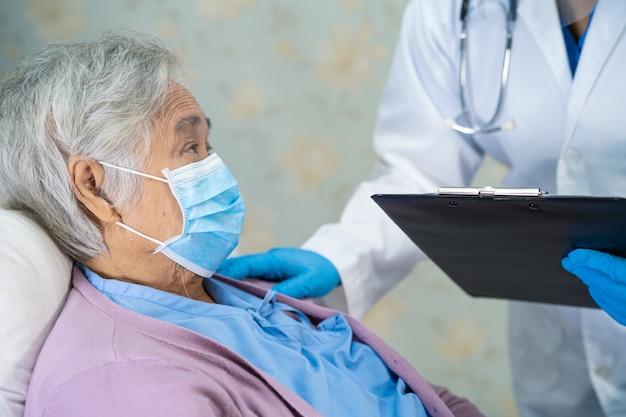 Medico asiatico che indossa una protezione per il viso e una tuta dpi per proteggere il coronavirus covid-19.