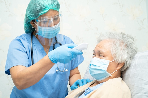 Medico asiatico che indossa una protezione per il viso e una tuta dpi per proteggere l'infezione da covid-19 coronavirus.