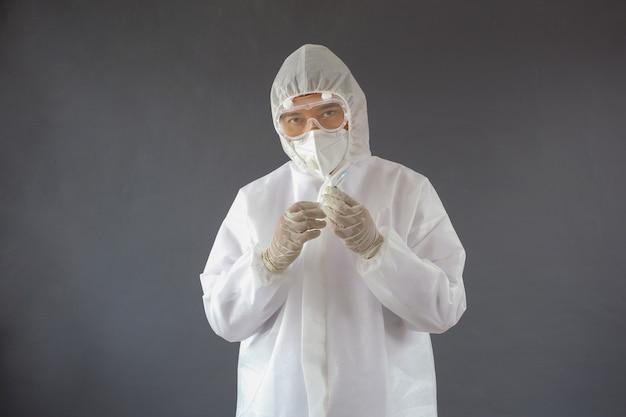 Medico asiatico che indossa una siringa di tenuta protettiva dpi