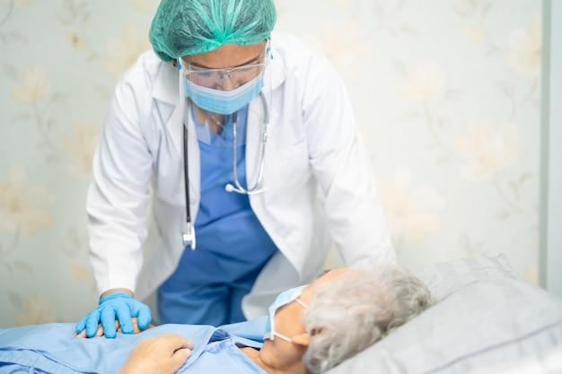 Medico asiatico che indossa una tuta dpi per proteggere il coronavirus covid-19.