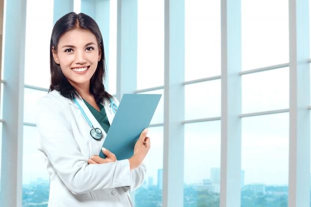 Donna asiatica di medico con lo stetoscopio che tiene una lavagna per appunti