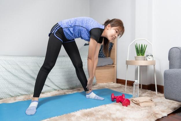 Asian facendo home fitness e yoga su un tappetino fitness facendo esercizio