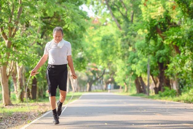 Uomo anziano asiatico o maschio anziano attivo e sano esercizio di salto con la corda nell'ambiente naturale del parco.