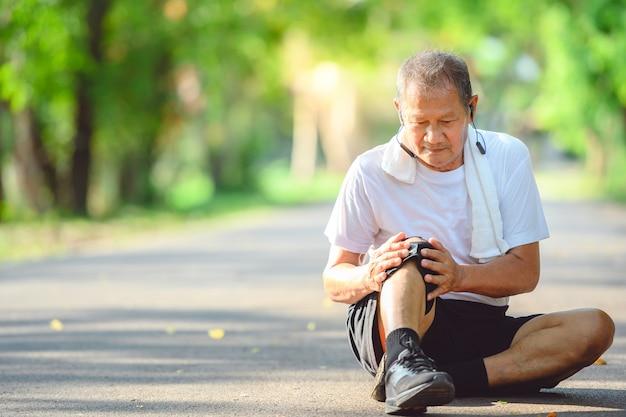 Uomo anziano asiatico o corridore anziano smetti di correre a causa di un infortunio al ginocchio. e metti una mano sul ginocchio che è stato ferito dalla corsa all'aperto e dalle passeggiate nel parco.