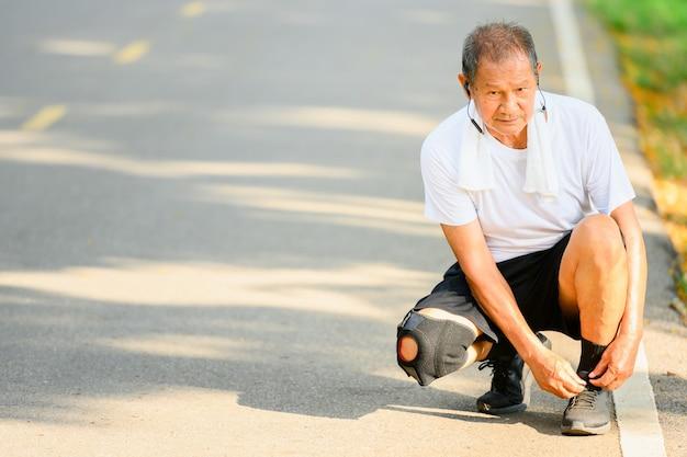Uomo anziano asiatico o corridore anziano lega i lacci delle scarpe per prepararti a fare jogging. nel jogging all'aperto e passeggiate nel parco.