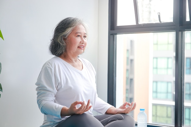 Donna anziana asiatica seduta a casa che si esercita, facendo pose di yoga. distanziamento sociale, esercizio per mantenere la salute degli anziani.