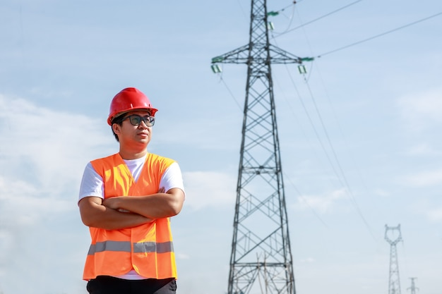 Ingegneri elettrici asiatici in uniforme di sicurezza standard in piedi in una centrale elettrica per ispezionare il palo dell'alta tensione elettrica.