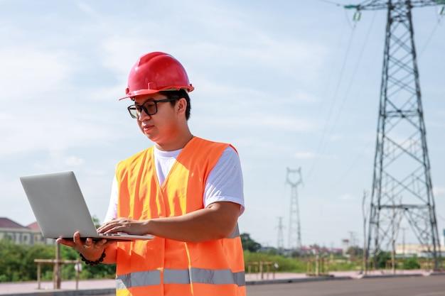 Ingegneri elettrici asiatici in uniforme di sicurezza standard che utilizzano un mobile in piedi in una centrale elettrica per ispezionare il palo dell'alta tensione dell'elettricità.