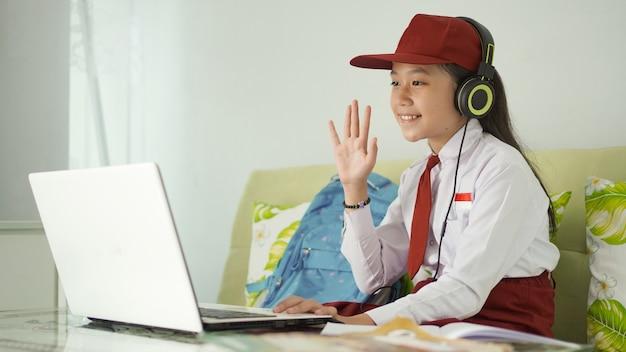 Ragazza asiatica della scuola elementare che impara a salutare online lo schermo del laptop a casa
