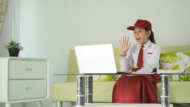Ragazza asiatica della scuola elementare che studia da casa saluta lo schermo del suo laptop
