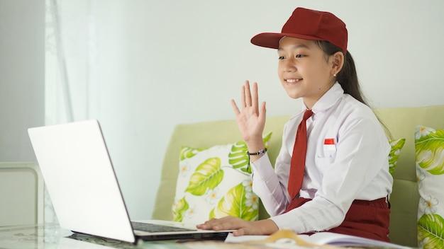Ragazza asiatica della scuola elementare che studia online a casa saluta lo schermo del laptop