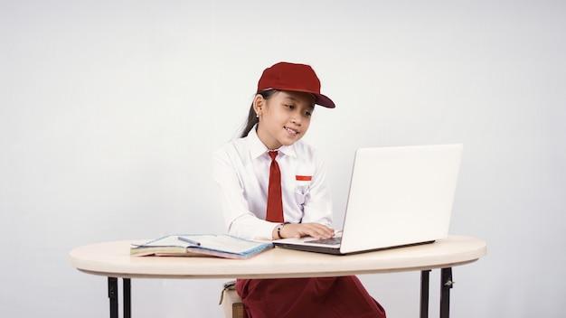 Ragazza asiatica della scuola elementare che studia online facendo uso del computer portatile isolato su fondo bianco