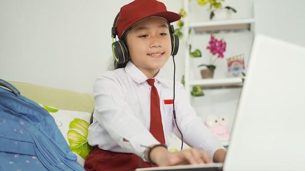 Ragazza asiatica della scuola elementare che studia online guardando lo schermo del laptop a casa