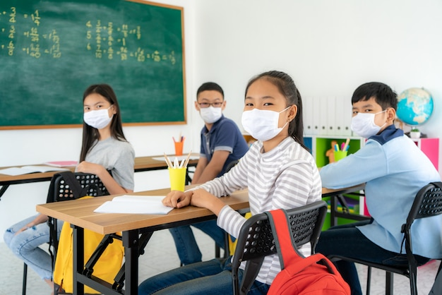 Studenti asiatici della scuola elementare che indossano maschera igienica