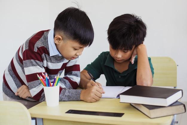 Studenti elementari asiatici che studiano e interagiscono in classe