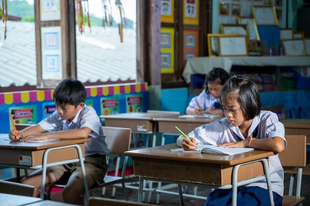 Studenti elementari asiatici in uniforme che studiano insieme in aula