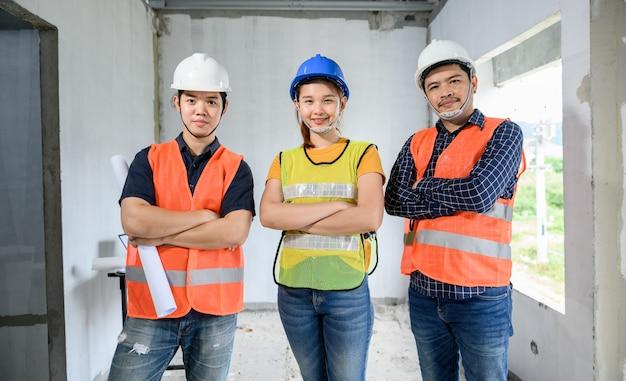 Gruppo sorridente dell'architetto e dell'ingegnere asiatico al sito della proprietà di costruzione. lavoro di squadra e progetto di costruzione di un complesso residenziale di successo