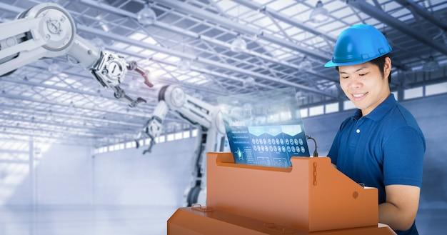 L'ingegnere o il tecnico asiatico sta lavorando con il braccio robotico di rendering 3d in fabbrica