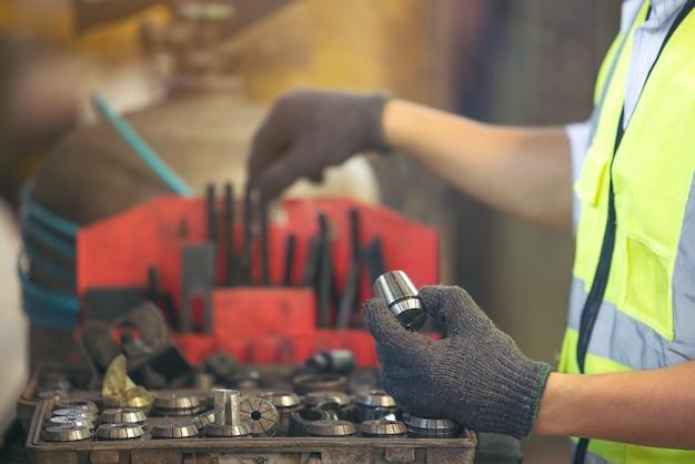 Controllo di qualità asiatico dell'operaio dell'ingegnere della macchina di servizio in fabbrica