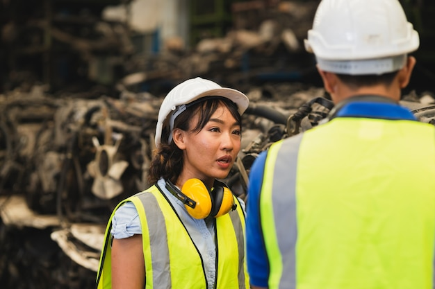 Ingegnere asiatico che lavora donne che lavorano insieme a un giovane uomo nel posto di lavoro dell'industria pesante che indossa una tuta di sicurezza del casco