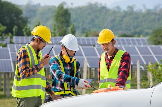 Ingegnere asiatico che lavora al controllo dell'attrezzatura nella centrale elettrica solare, energia pura, energia rinnovabile