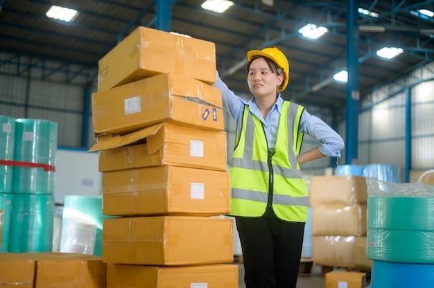 Una donna di ingegneria asiatica sta lavorando in un moderno magazzino