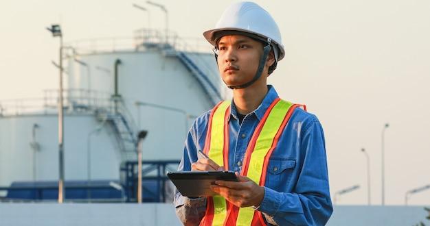 Ingegneria asiatica che lavora all'interno dell'impianto di raffineria di petrolio e gas