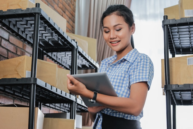 Donna asiatica dell'imprenditore con lo scaffale del pacchetto