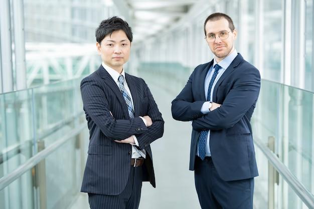 Uomini d'affari asiatici ed europei in piedi all'edificio aziendale
