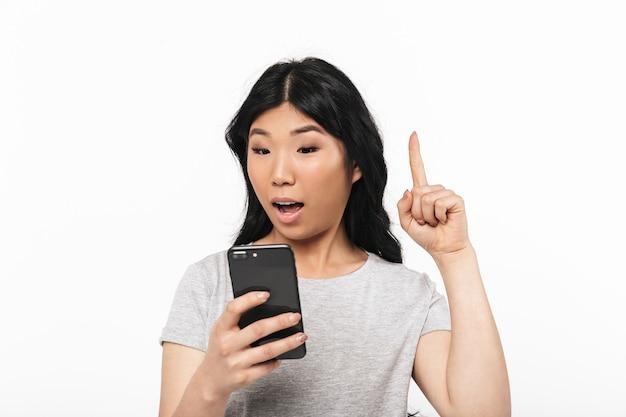Asiatico eccitato bella giovane donna in posa isolato sul muro bianco utilizzando il telefono cellulare ha un'idea.