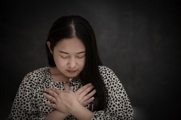 Donna asiatica faccia che prega e adora dio usando le mani per pregare nelle credenze religiose.