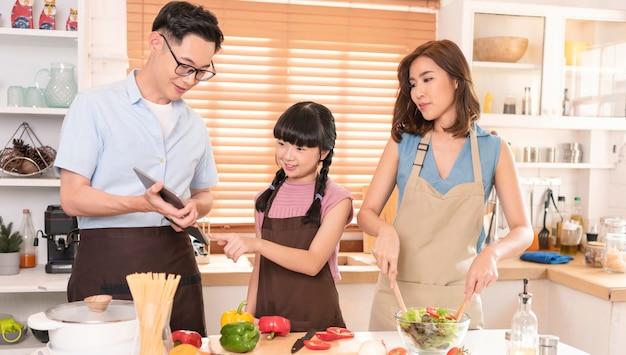La famiglia asiatica si diverte a cucinare insieme l'insalata in cucina a casa.
