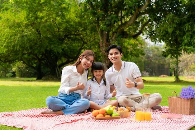 Famiglia asiatica che ha un picnic nel parco