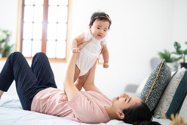 Famiglia asiatica e concetto di maternità felice sorridente giovane madre asiatica con un piccolo bambino a casa