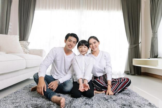 Il ritratto di famiglia asiatico con la gente felice che sorride esamina la macchina fotografica nella mia casa.