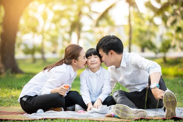 Il ritratto di famiglia asiatico con la gente felice che sorride esamina la macchina fotografica nel parco.