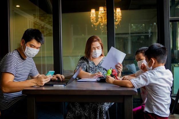 Famiglia asiatica in quarantena a casa durante il periodo di infezione da virus corona, covid-19