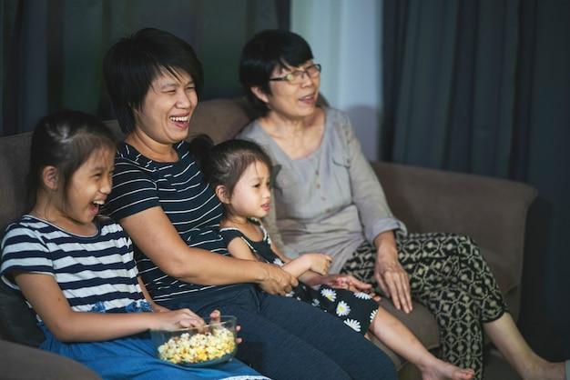 Famiglia asiatica che si siede su un divano accogliente e mangia popcorn mentre guarda un film in un salotto di casa. intrattenimento domestico, famiglia asiatica e tempo insieme concetto