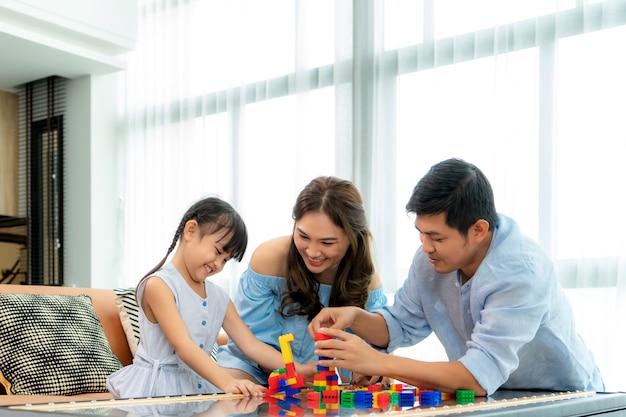 La famiglia asiatica trascorre il tempo nella sala giochi con padre, madre e figlia con i giocattoli in camera
