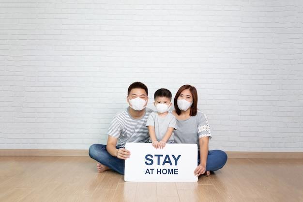 Famiglia asiatica che indossa una maschera medica protettiva per prevenire il virus covid-19 tenendo il libro bianco con stare a casa a portata di mano e seduti insieme sul pavimento a casa
