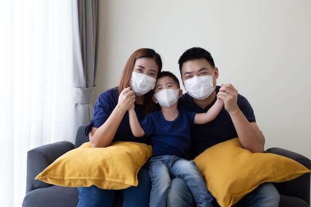 La famiglia asiatica che indossa la maschera medica protettiva per impedisce il virus