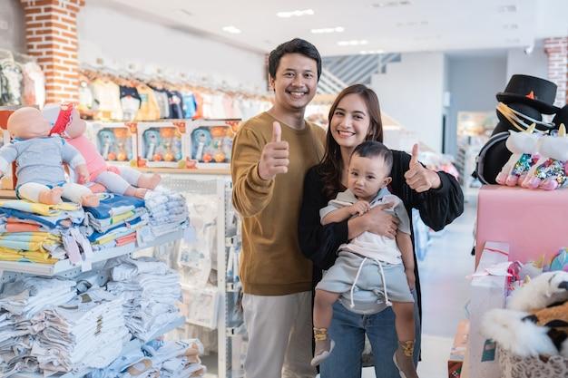 Famiglia asiatica con il suo bambino che fa shopping nel negozio per bambini con il pollice in su
