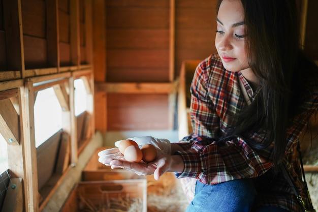 Coltivatore asiatico nell'allevamento di polli che tiene le uova di gallina