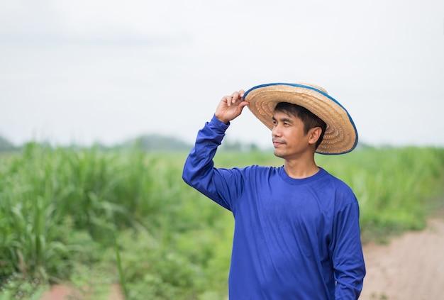 Uomo asiatico del coltivatore che tiene il cappello e che sta alla fattoria del riso.