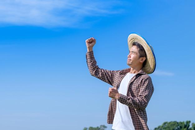 L'uomo asiatico del coltivatore posa felice e sorride con un cielo blu