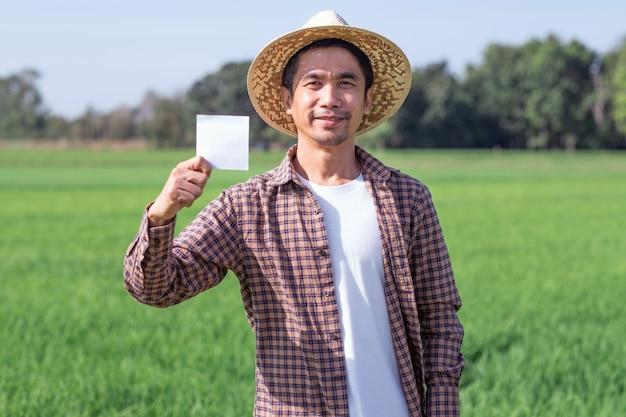 L'uomo asiatico del coltivatore posa la carta o la carta della tenuta con il fronte di sorriso all'aperto