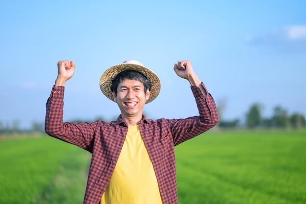 Fronte di sorriso dell'uomo del coltivatore asiatico e mani alzate che esaminano una fattoria del riso verde.