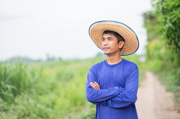 Uomo asiatico del coltivatore che sta e mani trasversali che esaminano il cielo alla fattoria verde