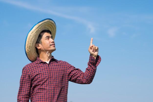 Uomo asiatico del coltivatore che sta guardando il lato superiore e alza la mano sopra il cielo